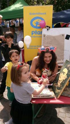 A young girl takes on the role of Frida Kahlo painting a self-portrait -