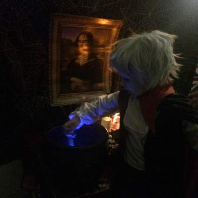 Count Dracula inspects the contents of a glowing witch's cauldron